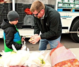 Kent-Ionia Labor Council Vice President Nathan Phillips (UA 174) loads produce with his son at the March food truck