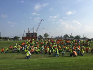 Over 200 site employees (Barton Malow Company, Holland Board of Public Works and contractors) walked over to Hope College and took a knee to say a prayer for the family of the man from Muskegon Roofing that died from a work site injury at Hope College yesterday. (Photo courtesy Holland Energy Park)